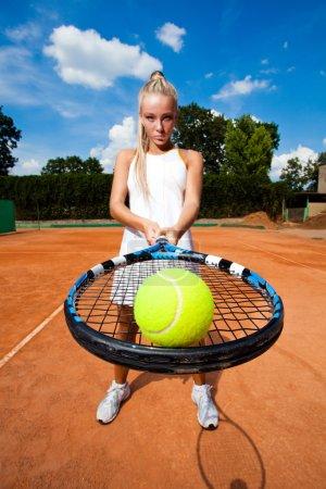 Photo pour Balle de tennis sur le racket à l'arrière-plan d'une belle jeune femme. gros plan - image libre de droit