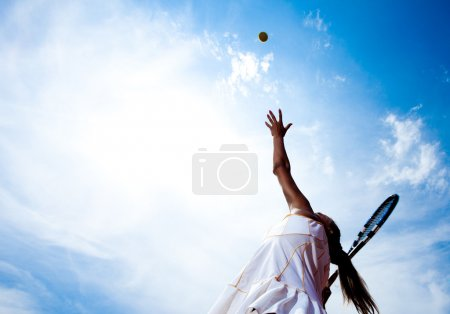 Photo for Tennis woman in a white tennis dress developing ball service - Royalty Free Image
