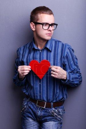 Photo pour Bel homme dans des lunettes tenant un cœur rouge dans ses mains - image libre de droit
