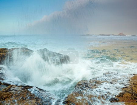 Stormy ocean and crashing waves on rocks