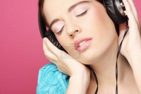 Photo pour Belle femme avec casque, elle écoute la musique sur fond rose - image libre de droit