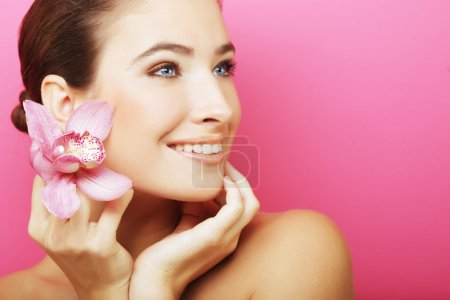 Photo for Beautiful happy woman with orchid flower over pink background - Royalty Free Image
