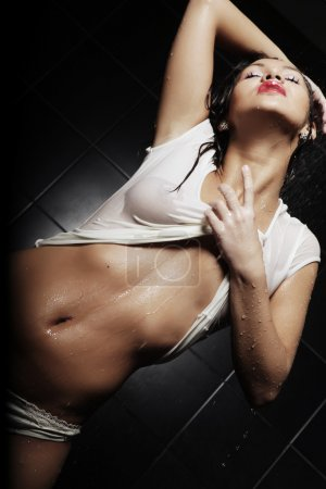 Photo for Young expressive sexy woman with T-shirt in water splashes and droplets - Royalty Free Image