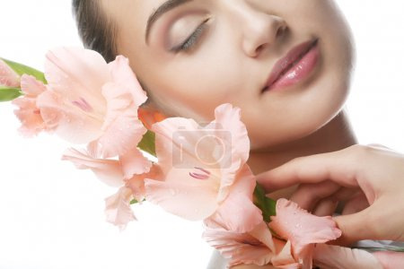 Photo for Close-up beautiful fresh face with pink gladiolus flowers in her hands - Royalty Free Image
