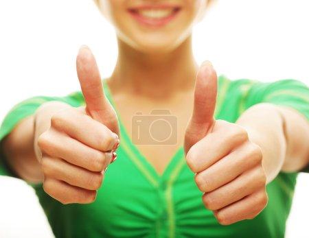 Photo pour Portrait d'une fille décontractée heureuse montrant les pouces vers le haut et souriant, sur fond blanc - image libre de droit
