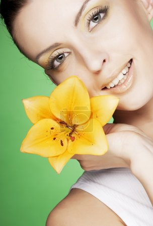 Photo for Beautiful girl with yellow flower over green background - Royalty Free Image