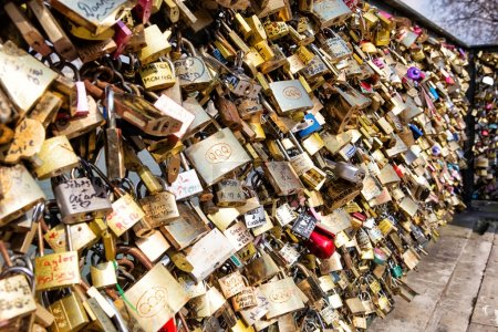 PARIS - MARCH 26: Love padlocks, a tradition of the romantic Paris, representing eternal love of the couples, who lock padlocks on a bridge over the Seine river in Paris, France,  MARCH 26, 2014