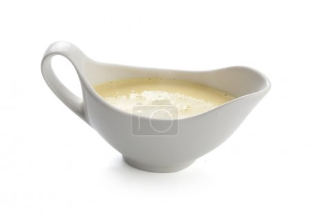 Photo for Creamy cheese sauce in the white sauceboat - Royalty Free Image
