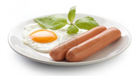 Two boiled sausages with fresh green basil and fri...