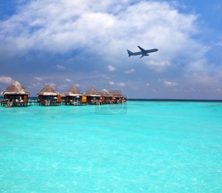 Lodges over water and the plane in the sky - tropical paradise