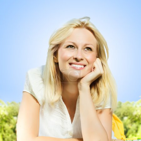 Photo for Happiness smiling blonde woman relaxing on green grass in the park, against clear blue sky . - Royalty Free Image