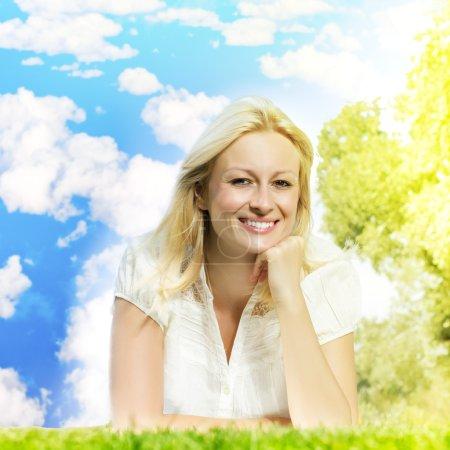 Photo pour Bonheur souriant femme blonde relaxant sur vert contre ciel bleu avec des nuages . - image libre de droit