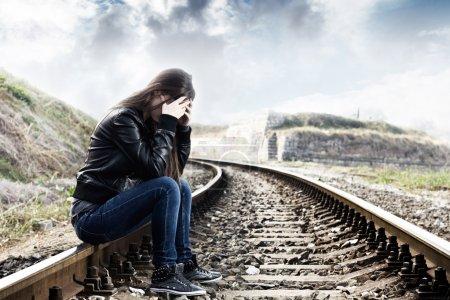 Photo pour Adolescente solitaire avec les mains sur le visage assis sur le chemin de fer - image libre de droit