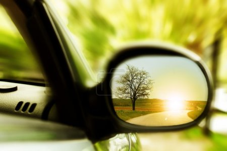 Photo for Sunset on a lonely country road, as seen in car mirror. - Royalty Free Image