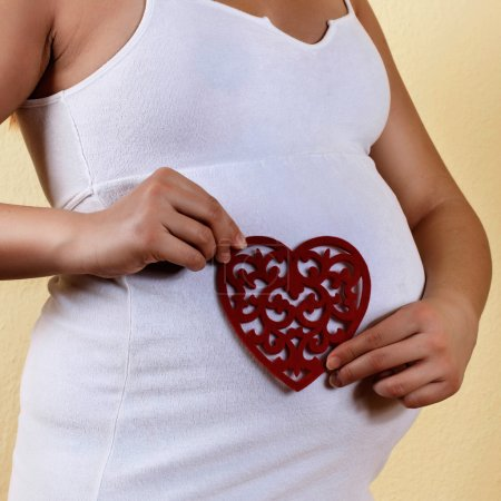 Photo for Pregnant woman holding heart shape over belly. - Royalty Free Image