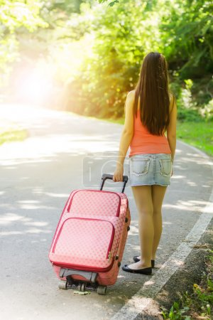 Photo for Attractive young woman with a suitcase ready for travel. - Royalty Free Image