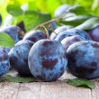 Fresh plums on wooden table...