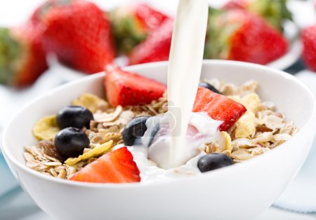 Photo for Milk pouring into bowl of cereals with fresh berries - Royalty Free Image