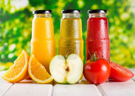 Photo pour Différentes bouteilles de jus avec des fruits sur la table en bois - image libre de droit