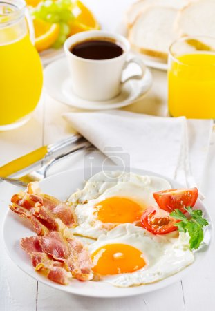 Photo for Breakfast with fried eggs, toasts, juice, coffee and fruits - Royalty Free Image