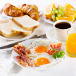 Breakfast with fried eggs, croissants, juice, coff...