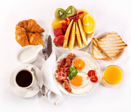 Photo for Breakfast with fried eggs, coffee, orange juice, croissant, toasts  and fruits - Royalty Free Image