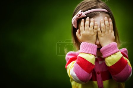 Photo for Little girl is playing hide-and-seek hiding face - Royalty Free Image