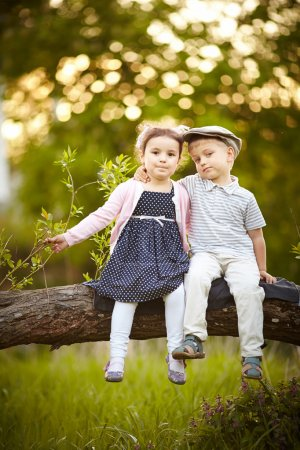 Photo for Little cute children sitting on tree. boy kissed girl - Royalty Free Image