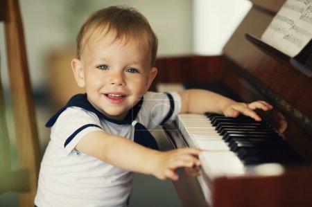 Foto de Niño gracioso toca el piano - Imagen libre de derechos