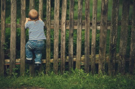 Photo pour Petit garçon drôle avec clôture à l'extérieur - image libre de droit