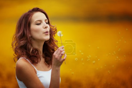 happy beautiful woman blowing dandelion