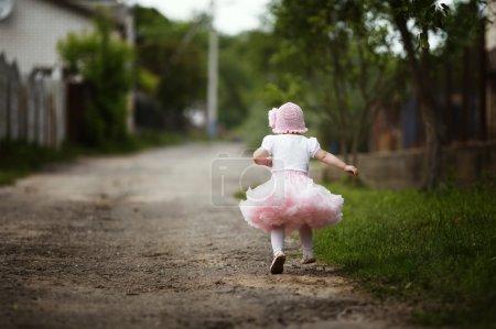 Photo pour Mignonne petite fille en robe s'enfuyant - image libre de droit