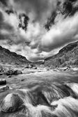 River landscape in drakensberg with dramatic clouds and mountain