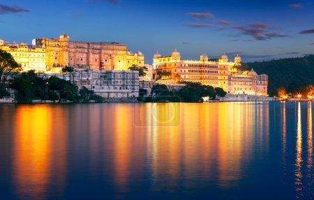 Pichola lake and City Palace at night. Udaipur, Ra...