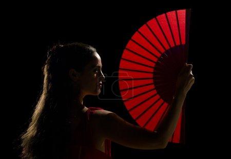 Photo for Female dancer holding a backlit red folding fan - Royalty Free Image