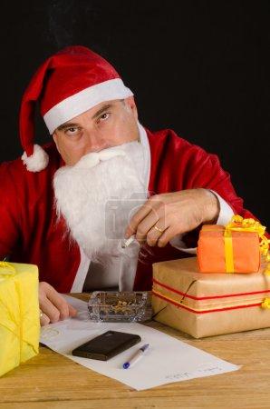 Photo pour Santa, surchargés de travail de prendre les commandes de la liste de souhaits, fume une cigarette - image libre de droit