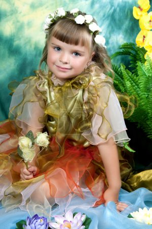 Beautiful girl in a light dress with wings in a wreath on a gree