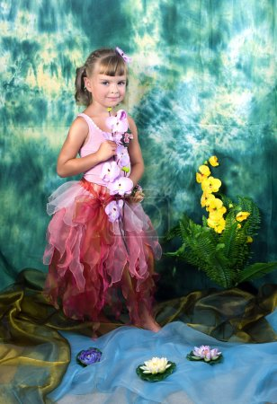 Beautiful girl in a pink dress with wings in a wreath on a green