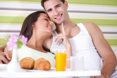Young couple eating breakfast in bed
