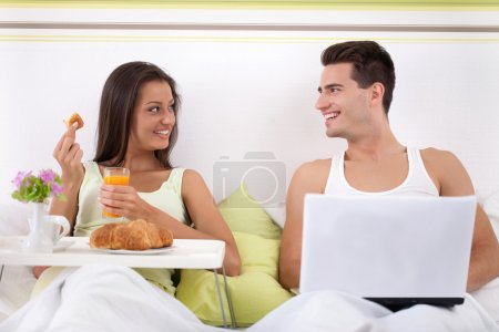 Couple sitting on bed in morning