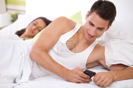 Photo for Cheating his wife, young men chatting with his mistress while his wife sleeps - Royalty Free Image