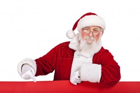 Photo for Santa Claus leaning on big red banner and pointing in it, isolated on white background - Royalty Free Image