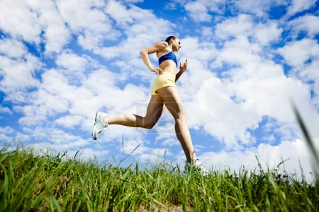Photo for Young woman running outdoor over blue sky - Royalty Free Image