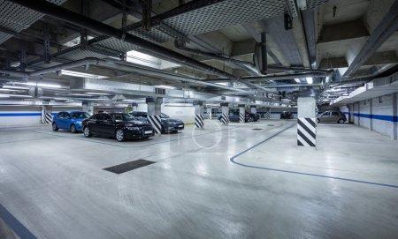 Photo pour Parking intérieur souterrain avec quelques voitures stationnées - image libre de droit
