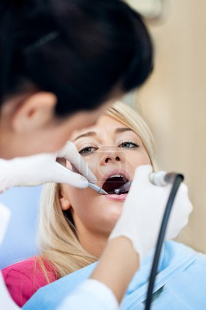 Photo pour Jeune femme ayant ses dents polies par un hygiéniste dentaire - image libre de droit