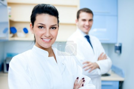Portrait of pretty female dentist arms crossed wit...