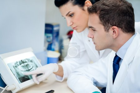 Photo for Dentis and assistant analyzing x-ray at the dental clinic - Royalty Free Image