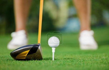 Photo pour Balle de golf et bâton avec les jambes de golfeur en arrière-plan - image libre de droit