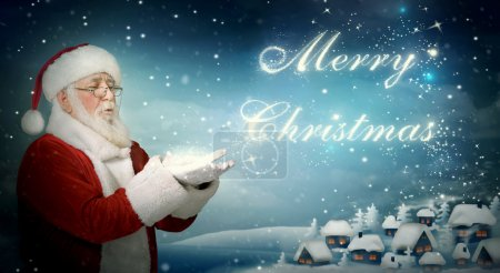 Photo for Santa Claus blowing 'Merry Christmas' from snow to little town - Royalty Free Image