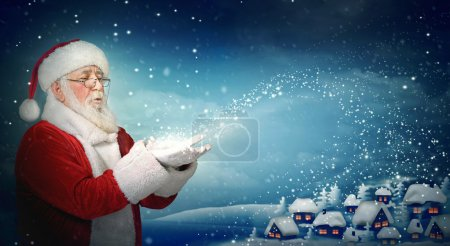 Photo for Santa Claus blowing snow to blue little town at night - Royalty Free Image